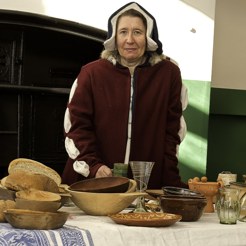 A lady in Tudor costume with a table of food