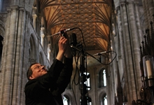 Ben Trenchard sets up a microphone in the quire