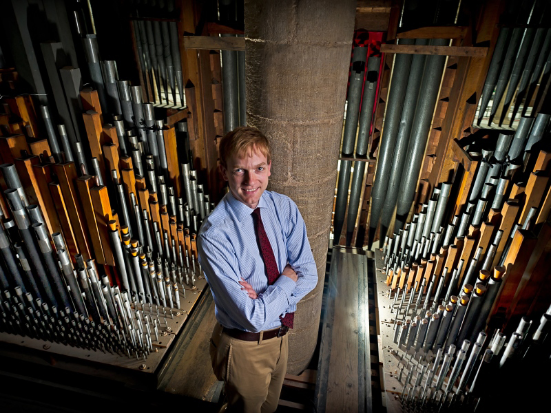 Former Director of Music, Robert Quinney, standing amongst the organ pipes