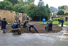 Volunteers spreading 50 tonnes of top soil in the rain